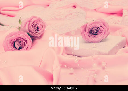 Gift box with roses on pink satin fabric surrounded by beads and white lace. Romantic vintage background. Selective - Stock Photo