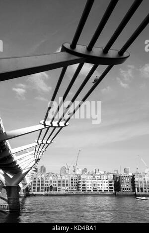 Black and White Monochrome Image of the Millenium Footbridge Southwalk London England Crossing the River Thames - Stock Photo