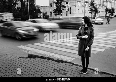 One teenage girl blue coat standing at the traffic light on city street on a cloudly autumn day with vehicles passing - Stock Photo