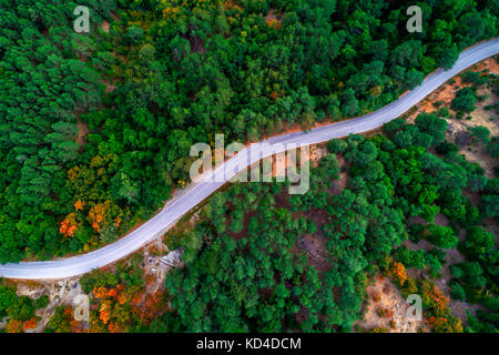 Aerial view of drone over mountain road going through forest landscape. - Stock Photo