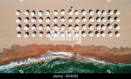 Aerial top view on the beach. Umbrellas, sand and sea waves - Stock Photo