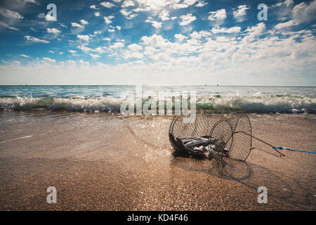 Fishing net coop trap , a floating basket for keeping live fish in water. - Stock Photo