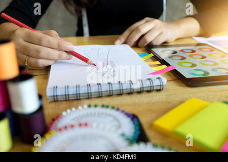 young fashion designer work with fabric cloth on the wood table - Stock Photo