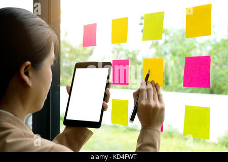 Businesswoman use tablet and looking to Note paper reminder schedule project on glass window ,with tablet clipping - Stock Photo