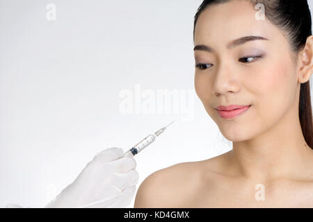 doctor hand use  Syringe injection  to woman face  concept healthcare for beauty she need or not - Stock Photo