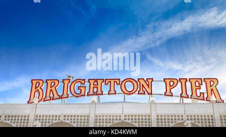 Brighton Pier sign in neon illuminated letters against blue sky, Brighton Pier, Brighton, East Sussex, England - Stock Photo