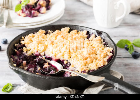 Coconut crumble in cast iron pan with fresh apples and blueberry. Healthy food concept. - Stock Photo