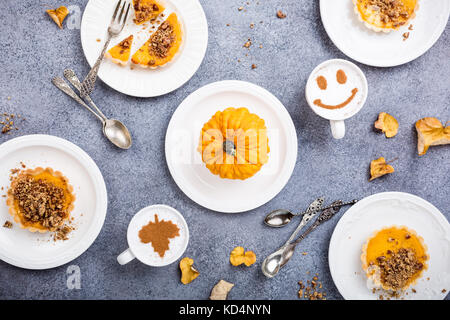 Thanksgiving day concept with homemade pumpkin tartlet, mini pie, on gray stone background. Healthy autumn food - Stock Photo