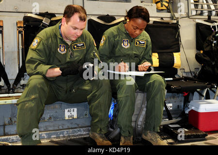 U.S. Air Force Senior Airman Robert Deal and Staff Sgt. Ann Roberts perform calculations for proper restrainment - Stock Photo