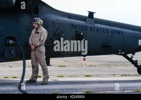 U.S. Marine Cpl. Jason D. Moxley, assigned to the 273rd Marine Wing Support Squadron, Air Operations Company, waits as a UH-60 Blackhawk is fueled during forward air refueling point operations at McEntire Joint National Guard Base, S.C. on May 14, 2014. Elements of the South Carolina Air and Army National Guard and the U.S. Marines conduct joint operations which are crucial to the ongoing success of operational readiness and deployments around the world.  (U.S. Air National Guard photo by Tech Sgt. Jorge Intriago/Released) Stock Photo