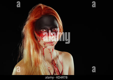 Mystic hero, bloody girl with blood on her face on a dark background. Fantasy horrible and Halloween makeup. - Stock Photo