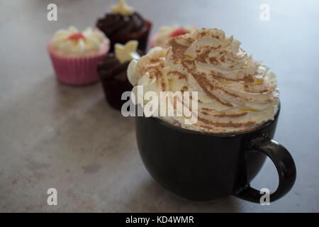 Strawberry and Chocolate Cupcakes Accompanied by Hot Chocolate with Cream and Chocolate dusting. - Stock Photo