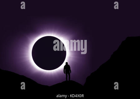 Full Solar Eclipse With Man Standing On Mountain In Foreground - Stock Photo