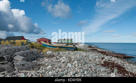 Lobster Boats on a Rocky Beach in Newfoundland:  Small fishing boats sit  amid stacked lobster traps on the rocky - Stock Photo