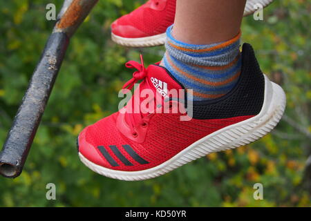 A pair of red youth Adidas sport shoes dangling from the feet of a young person riding a chairlift in Gatineau Park, - Stock Photo