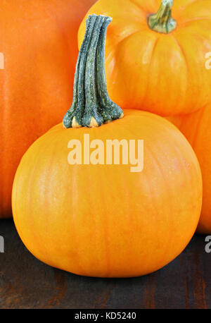 A stack of Halloween pumpkins on a rustic wooden table. - Stock Photo