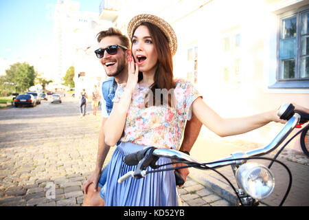 Happy young couple going for a bike ride on a summer day in the city.They are having fun together. - Stock Photo
