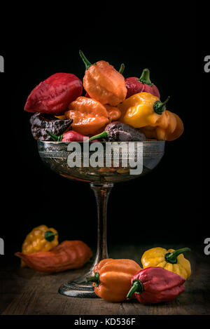 different kinds of hot  chili peppers on silverware on black background - Stock Photo