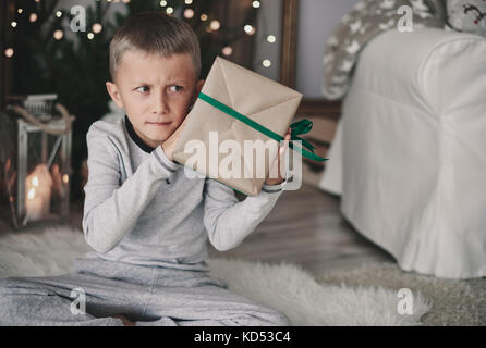 Boy shaking a wrapped present - Stock Photo