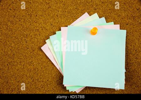 A yellow sticky note writing, caption, inscription colorful sticky notes on cork bulletin board - Stock Photo