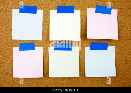 A yellow sticky note writing, caption, inscription Cork board with six blank colorful sticky notes. - Stock Photo