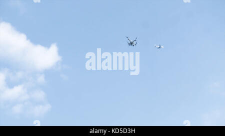 Drone flying in the sky above him flies the plane. Flying quadrocopter drone in the sky with mounted digital camera - Stock Photo