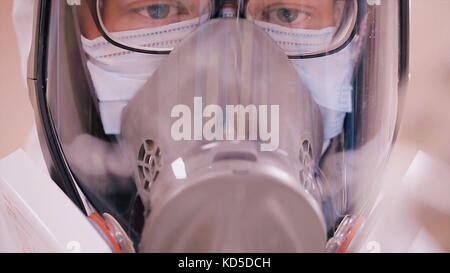 Scientist in protective clothing with respirator. Infection control concept. Scientist in protective suit and gas - Stock Photo