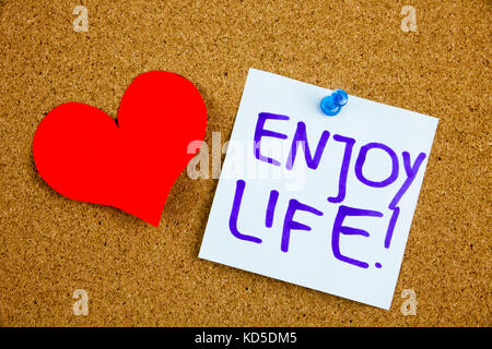 A yellow sticky note writing, caption, inscription enjoy life, motivational lifestyle reminders against black ext - Stock Photo