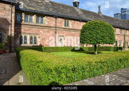 A nice square with trees and hedges next to Chetham's library in Manchester on a sunny day - Stock Photo