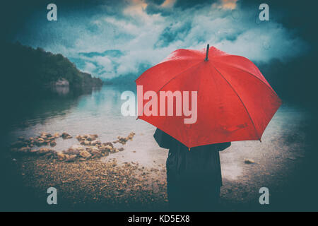 Woman with red umbrella contemplates on rain in front of a lake. Sad and lonely female person looking into distance. - Stock Photo