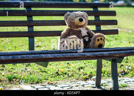 Abandoned teddy bear left outdoors, to find a new owner - Stock Photo
