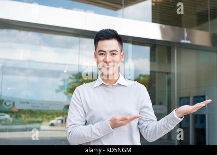 Handsome businessman with arm out in a welcoming gesture - Stock Photo