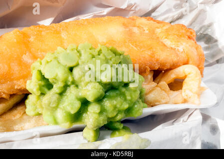 Fish and chips with mushy peas, wrapped in paper from a takeaway, UK. - Stock Photo