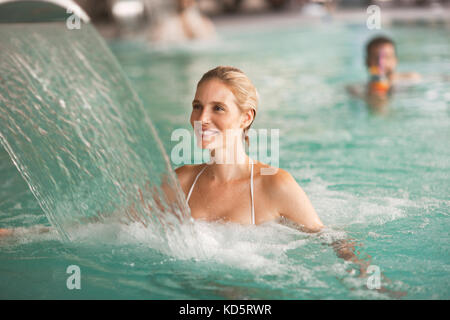 Portrait of beautiful woman relaxing in swimming pool - Stock Photo