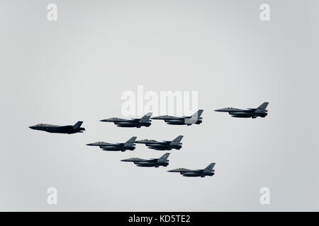 One F-35 and seven F-16 fighter jets in formation at the air show of the Royal Netherlands Air Force at the military - Stock Photo