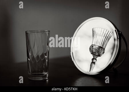 Ordinary glass is looking in a mirror. The reflection is on a beautiful crystal glass. - Stock Photo