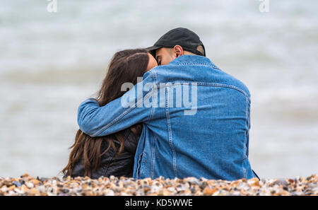 Young couple sitting on a beach kissing and embracing each other. Young lovers hugging on the beach. - Stock Photo