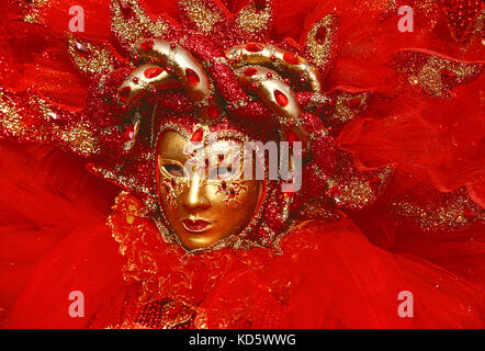 Italy. Venice. Carnival. Person in red costume. Close up of face with gold mask. - Stock Photo