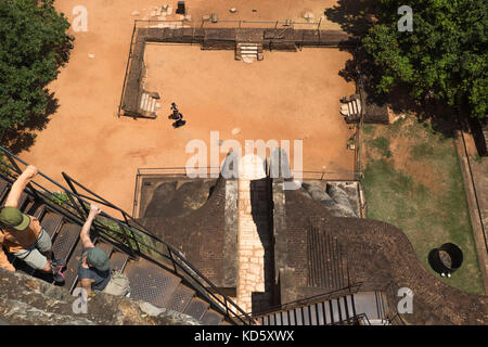 Sigiriya, Sri Lanka - March 23 2017: Tourist climbing down the stairs from Lions Rock, high angle view on the entrance - Stock Photo