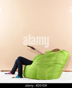 Pre teen girl in bean bag chair with tv remote - Stock Photo