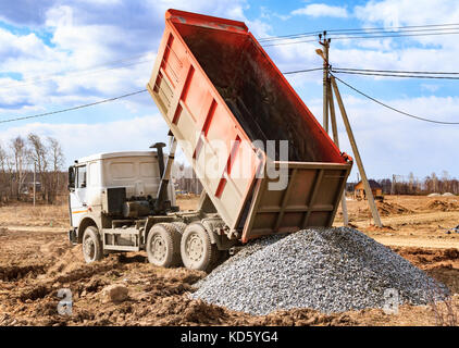 Dumptruck in action on a construction site - Stock Photo