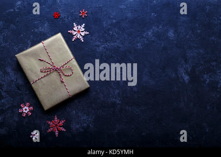 Vintage gift box wrapped in golden craft paper on black stone background. Christmas holiday concept, view from above - Stock Photo