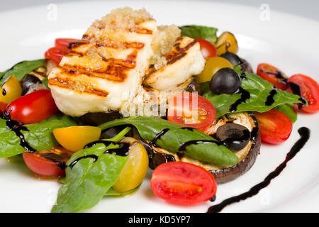 Grilled Halloumi Cheese poured with garlic olive oil salad witch grilled eggplant, cherry tomatoes, black olives - Stock Photo