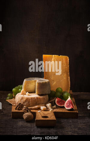 Cheese board, fruits and nuts on the rough wood - Stock Photo
