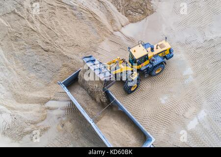 Yellow wheel loader loading sand on dumper truck. Sand quarry - Stock Photo
