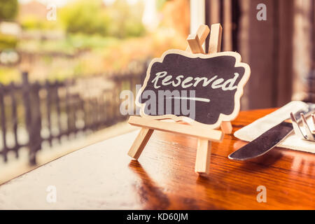 a cute wooden blackboard, chalkboard, easel as a reserved sign on a round wooden table by a window with a view in - Stock Photo