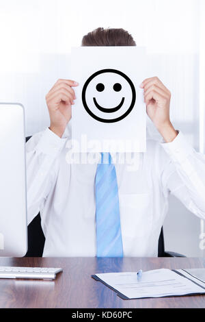 Close-up Businessman Holding Smile Emotion On Paper Over Face - Stock Photo
