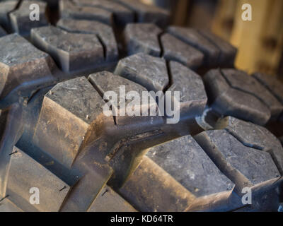 Closeup of aggressive offroad mud tire tread on 4x4. - Stock Photo