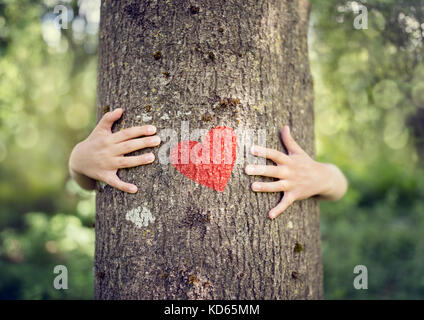 Tree hugging, little boy giving a tree a hug with red heart concept for love nature Stock Photo