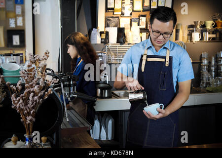Portrait of barista making latte or cappucino coffee in coffee shop. Cafe restaurant service, Small business owner, - Stock Photo